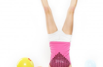 young happy woman standing on her head over white