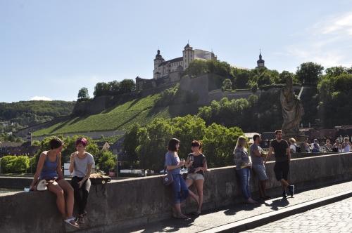 橋の上で、近くのレストランで注文した白ワインのグラスを傾ける人々。