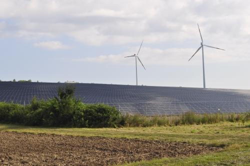"""突如として現れる""""ソーラーパネル畑""""と風力発電の風車。"""