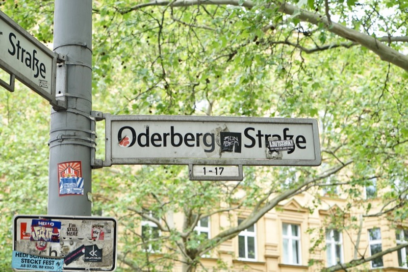 ストリートの始まりと終わりには必ず名前を示す標識があります。Oderbergerの「er」部分がいたずらでシールが貼られていますが……。